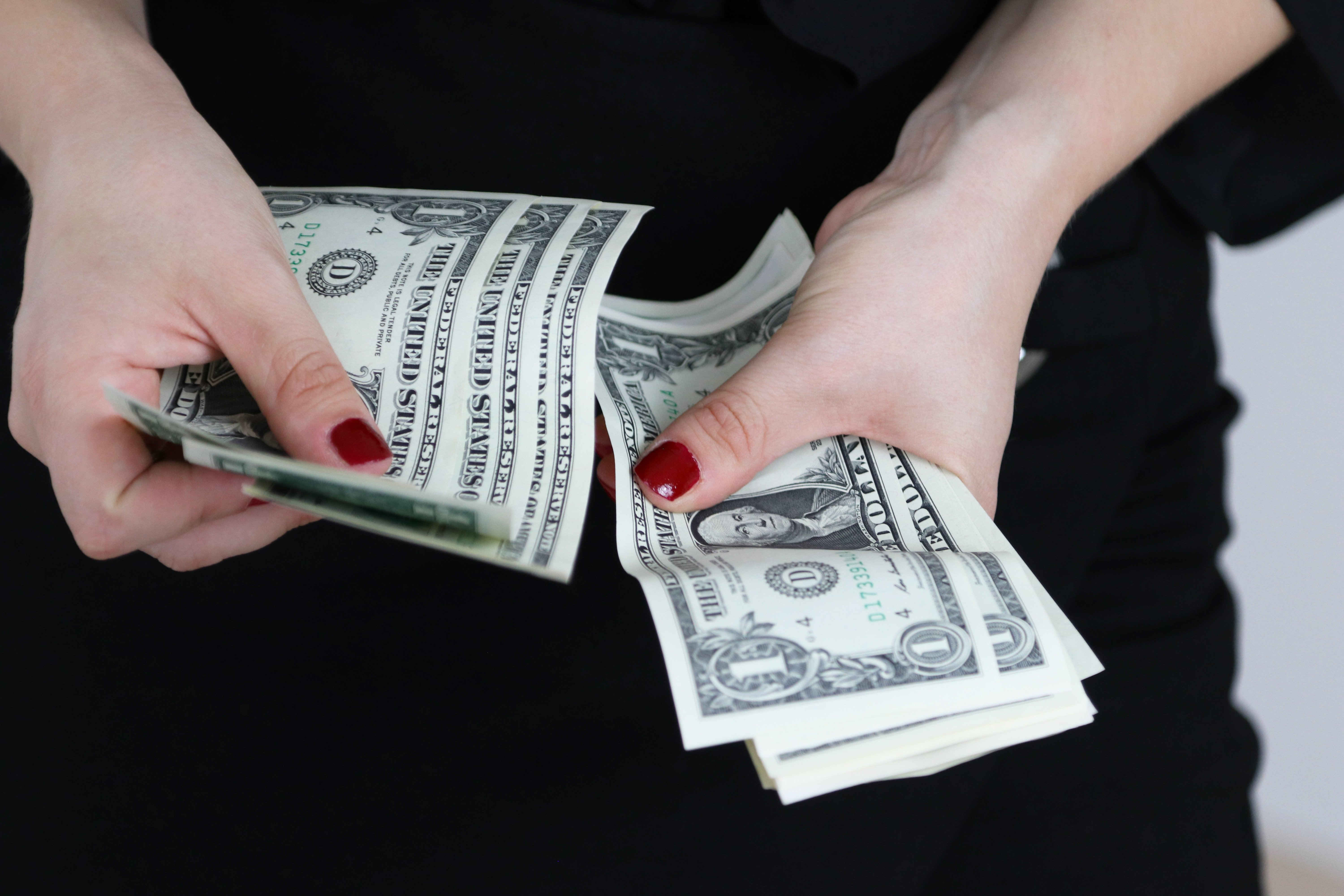 woman with red nail polish counting one dollar bills
